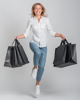 Vooraanzicht van smileyvrouw met veel boodschappentassen