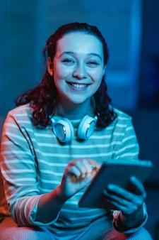 Vooraanzicht van smileyvrouw thuis met hoofdtelefoons en tablet