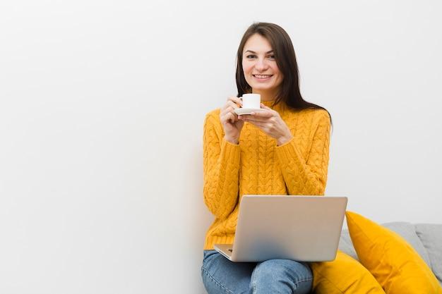 Vooraanzicht van smileyvrouw zittend op een bank en een kopje koffie met laptop op schoot te houden