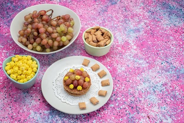 Vooraanzicht van snoep en druiven op de kleurrijke ondergrond
