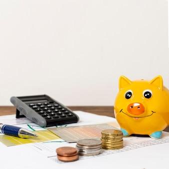 Vooraanzicht van spaarvarken en stapels munten