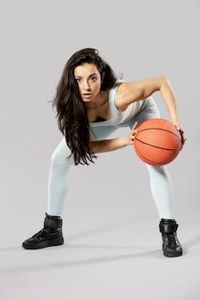 Vooraanzicht van sportieve vrouw met basketbalbal