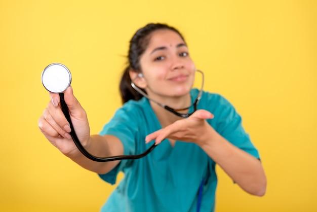 Vooraanzicht van stethoscoop in vrouwelijke hand op gele geïsoleerde muur