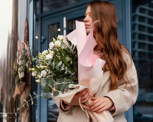 Vooraanzicht van stijlvolle vrouw buitenshuis met een boeket bloemen