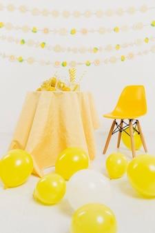 Vooraanzicht van tafel en stoel met ballonnen en citroenen