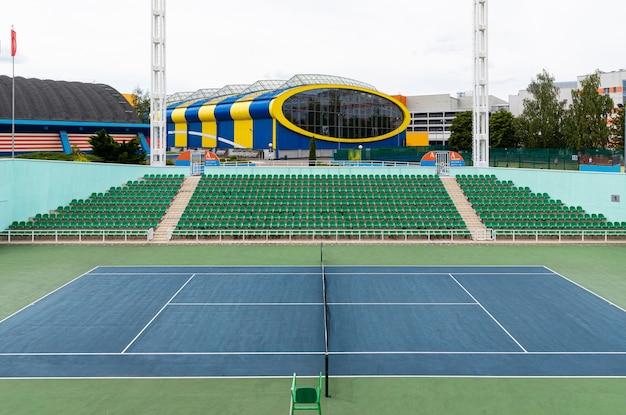 Vooraanzicht van tennisbaan in open ruimte met de bouw van het tenniscentrum bij