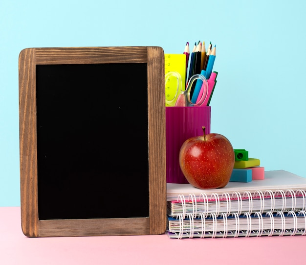 Vooraanzicht van terug naar schoolbenodigdheden met schoolbord en potloden