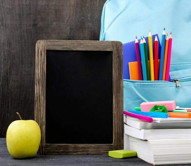 Vooraanzicht van terug naar schoolkantoorbehoeften met appel en bord