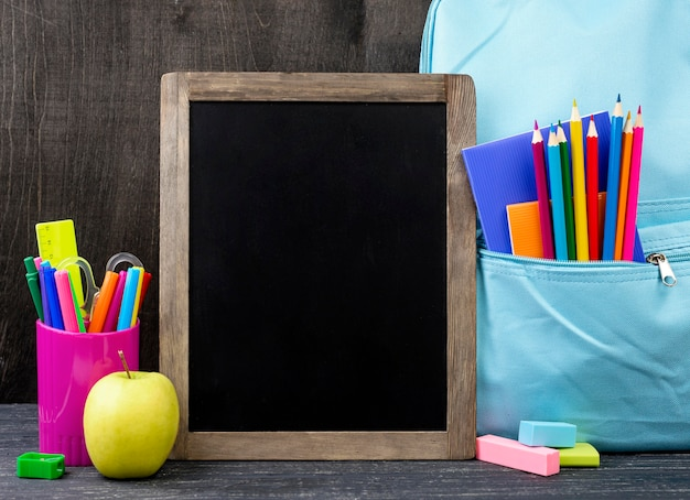 Vooraanzicht van terug naar schoolkantoorbehoeften met kleurrijke potloden en bord