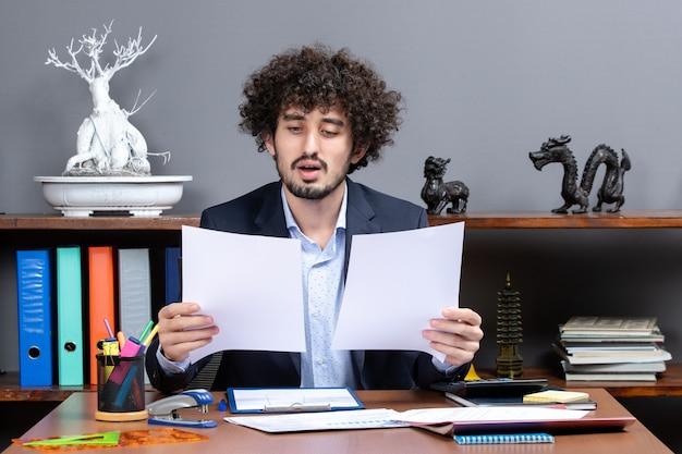 Vooraanzicht van tevreden jonge zakenman die op kantoor werkt