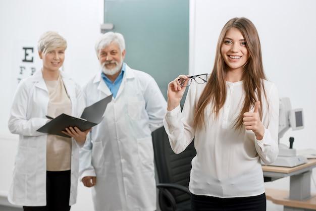 Vooraanzicht van tevreden patiënt die voor oude oogarts en medewerker glimlacht.