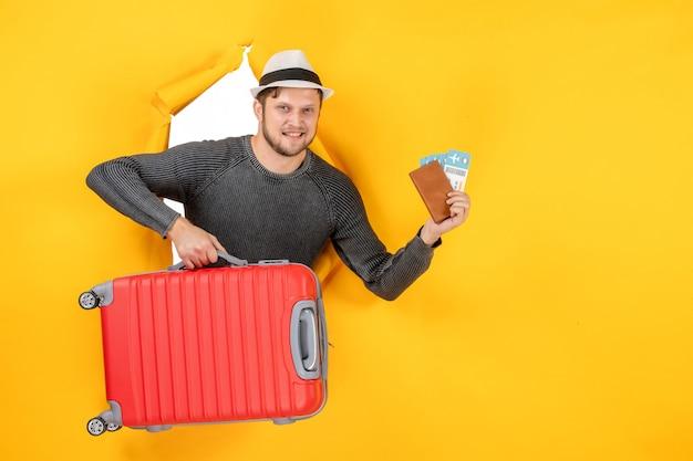 Vooraanzicht van tevreden volwassen holdingstas en buitenlands paspoort met kaartje in een gescheurd op gele muur