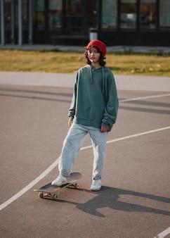Vooraanzicht van tiener buiten met skateboard
