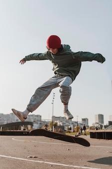 Vooraanzicht van tiener met buiten skateboard