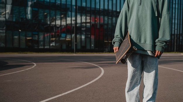 Vooraanzicht van tiener met skateboard buitenshuis en kopieer de ruimte