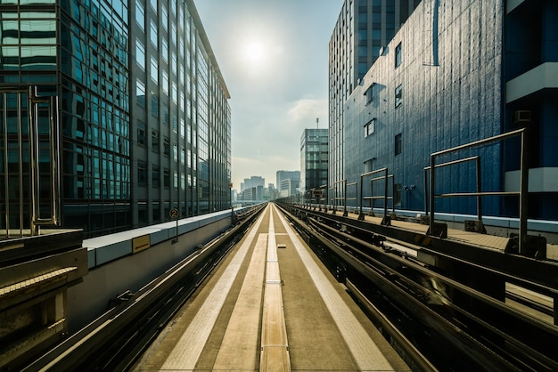 Vooraanzicht van trein in moderne stad. recht spoor met de achtergrond van stadsgebouwen.