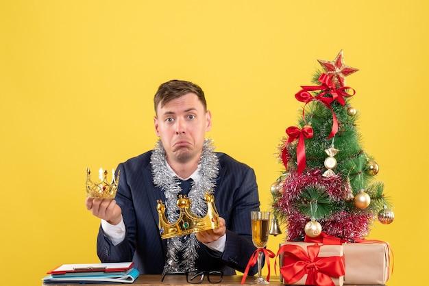 Vooraanzicht van trieste zakenman met kronen zittend aan de tafel in de buurt van kerstboom en presenteert op geel