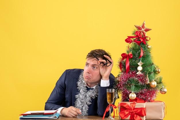 Vooraanzicht van trieste zakenman zittend aan de tafel in de buurt van kerstboom en presenteert op geel