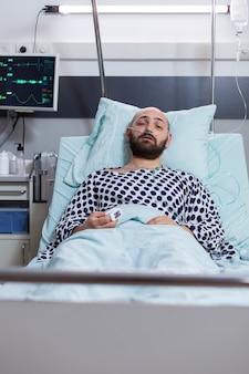 Vooraanzicht van trieste zieke man met neuszuurstofbuis met luchtwegaandoening die in bed rust tijdens therapiebehandeling