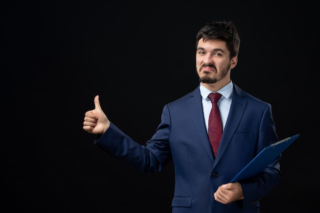 Vooraanzicht van trotse en ambitieuze mannelijke kantoormedewerker in pak die documenten vasthoudt en een goed gebaar maakt op geïsoleerde donkere muur