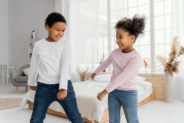 Vooraanzicht van twee broers en zussen die thuis samen dansen