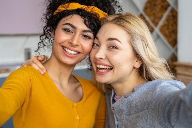 Vooraanzicht van twee gelukkige vrouwen die een selfie nemen