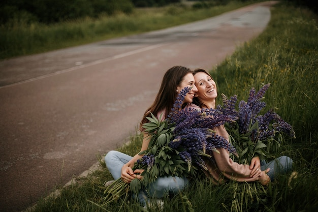 Vooraanzicht van twee jonge brunette meisjes die op gras zitten met grote verse boeketten van wilde lupines in de buurt van de weg en oprecht glimlachen