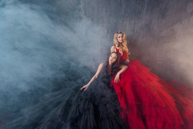 Vooraanzicht van twee mooie vriendinnen in weelderige jurken