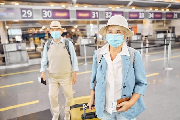 Vooraanzicht van twee passagiers met gezichtsmaskers en instapkaarten die op de luchthaven staan