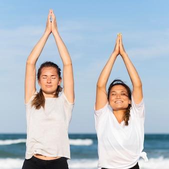 Vooraanzicht van twee smiley vrouwelijke vrienden die samen op het strand uitwerken