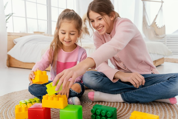 Vooraanzicht van twee smileyzusters die met speelgoed thuis spelen Gratis Foto