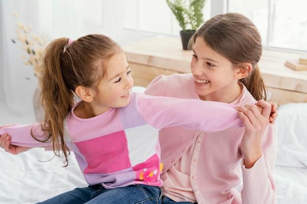Vooraanzicht van twee smileyzusters die thuis samen spelen Premium Foto