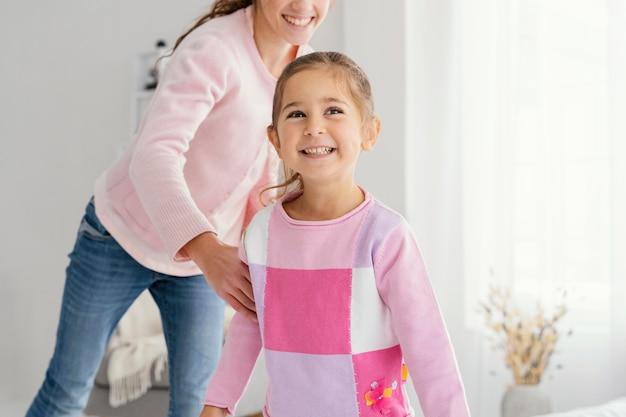 Vooraanzicht van twee smileyzusters die thuis spelen Premium Foto