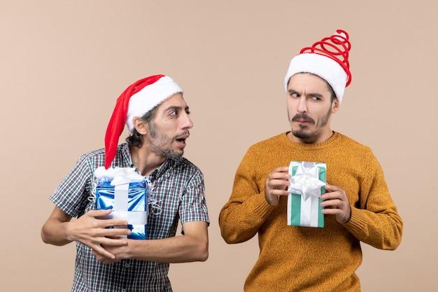Vooraanzicht van twee verwarde jongens die kerstmutsen dragen en cadeautjes op beige geïsoleerde achtergrond houden
