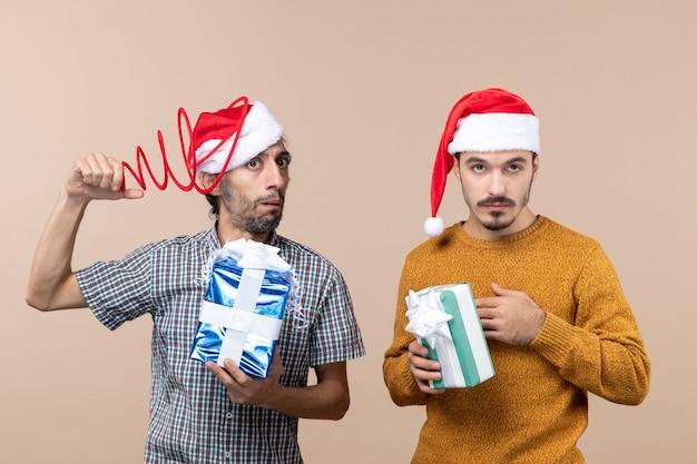 Vooraanzicht van twee verwarde jongens met kerstmutsen, één met zijn kerstmuts en de andere met zijn hand op zijn borst op beige geïsoleerde achtergrond