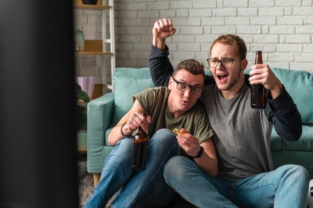 Vooraanzicht van twee vrolijke mannelijke vrienden die op tv naar sport kijken en bier hebben