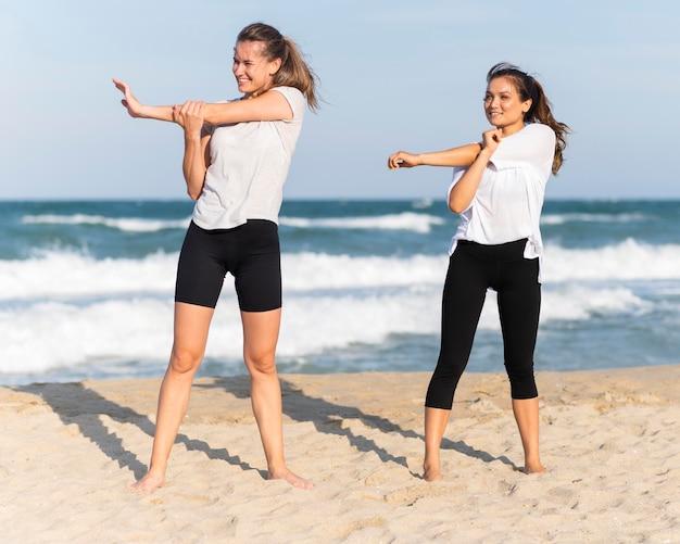 Vooraanzicht van twee vrouwelijke vrienden die samen op het strand trainen