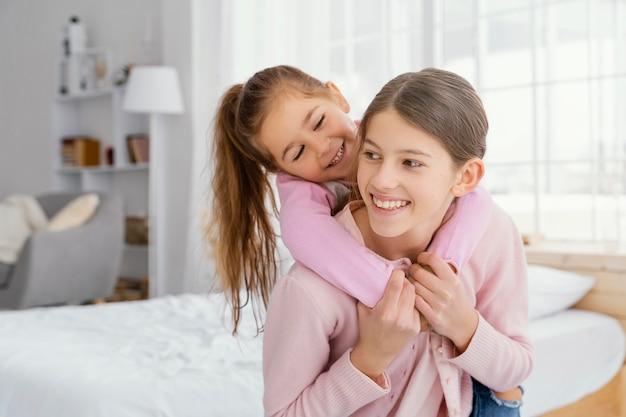 Vooraanzicht van twee zusjes samen thuis