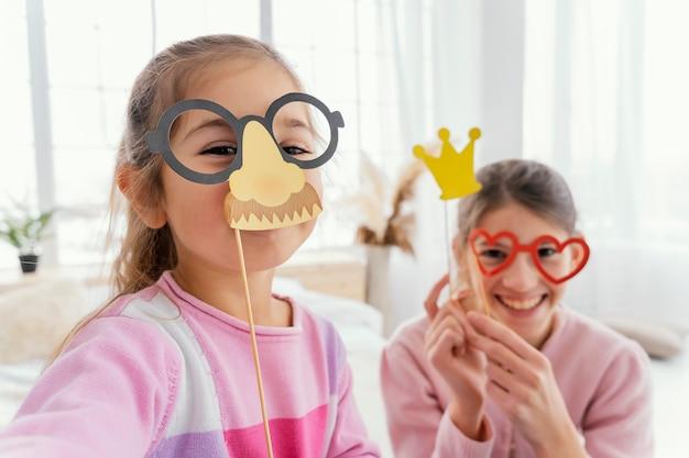 Vooraanzicht van twee zussen die thuis leuke selfie nemen