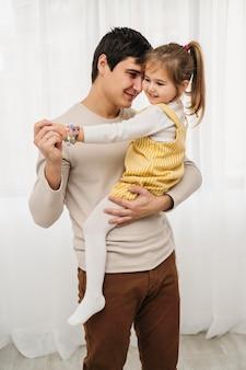 Vooraanzicht van vader die zijn dochter houdt