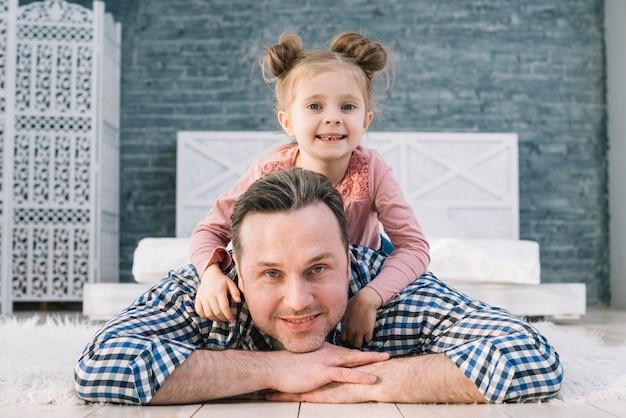 Vooraanzicht van vader die zijn dochter op rug thuis vervoeren