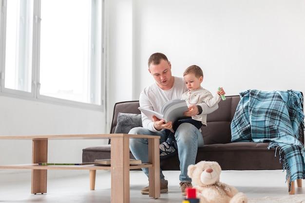 Vooraanzicht van vader die zoon en het lezen houdt