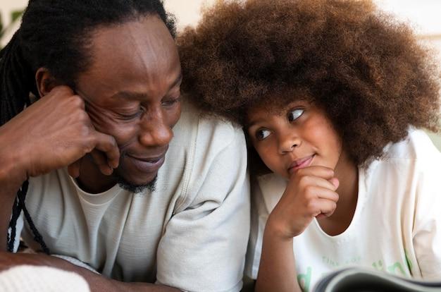 Vooraanzicht van vader en dochter die samen een boek lezen