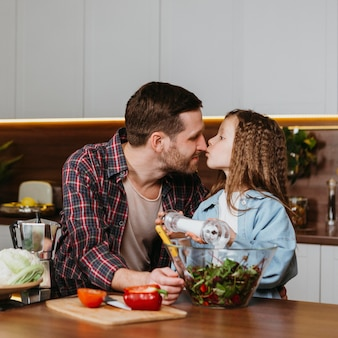 Vooraanzicht van vader en dochter die voor een kus gaan tijdens het bereiden van voedsel in de keuken