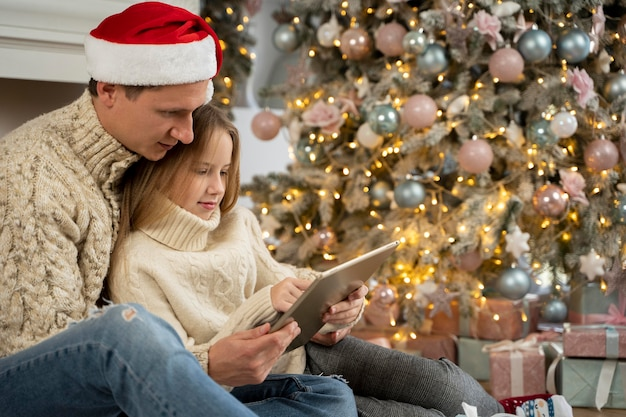 Vooraanzicht van vader en dochter op tablet Gratis Foto