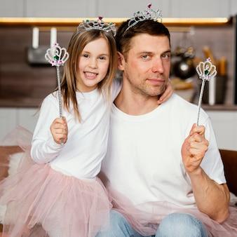 Vooraanzicht van vader en dochter spelen met tiara en toverstaf