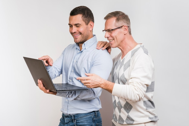 Vooraanzicht van vader en zoon die laptop bekijken