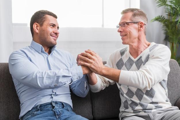 Vooraanzicht van vader en zoon hand in hand
