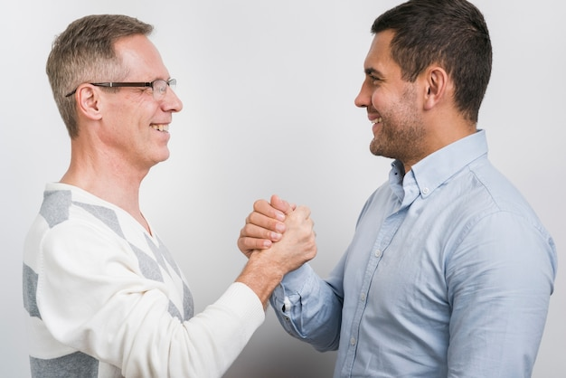 Vooraanzicht van vader en zoon handen schudden