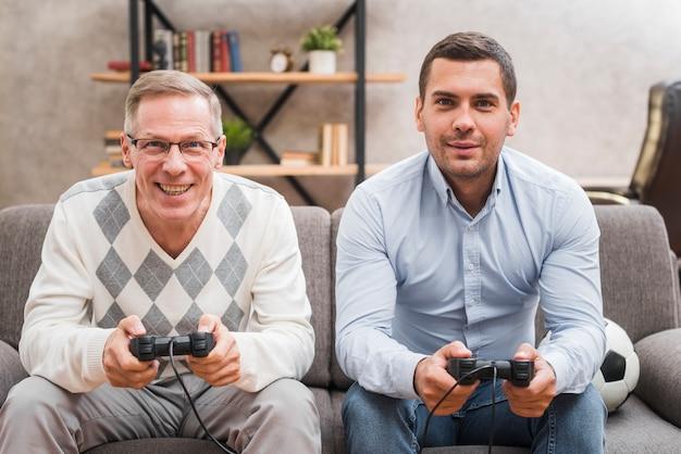 Vooraanzicht van vader en zoon spelen met joysticks